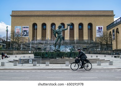 GOTHENBURG, SWEDEN - MAY, 2017: Cyclist riding a bike in front of Poseidon Fountain in Gothenburg, Sweden.
