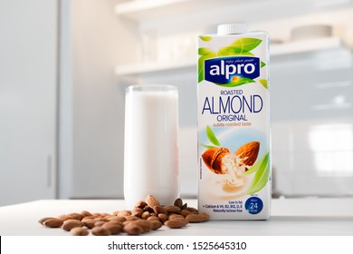 Gothenburg, Sweden - October 08, 2019: Alpro Roasted Almond milk, filled glass and almonds on kitchen counter