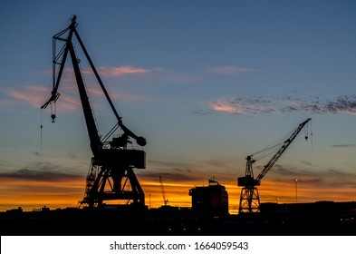 Gothenburg, Sweden, September 5, 2016. Silhouettes of large lifting cranes in Gothenburg harbor during dusk. The sky is blue and orange. Evening light background with copy space, place for text.