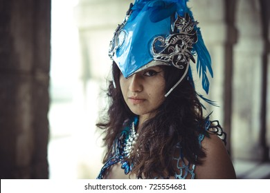 Gothic, beautiful latin woman dressed in blue feather suit and helmet simulating an exotic bird in a place in autumn