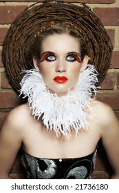 Gothic beautiful woman with feather necklace and false lashes wearing red lips