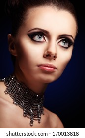 Gothic beautiful woman with giant pretty blue eyes and evening makeup on black background looking up to the right side