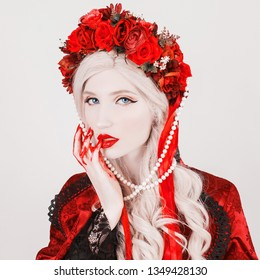Gothic blonde woman vampire in flower wreath with pale skin and red lips. Vampire from nightmare with blood. Gothic witch in wreath with ribbons. Terrible blonde witch. Nightmare woman. Blood fingers