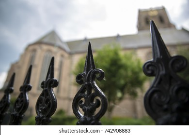 A gothic church with a black cast iron fence and a blue sky in the Netherlands.