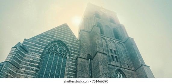 A Gothic church tower on a cold morning in the blue mist with the sun barely shining through the fog