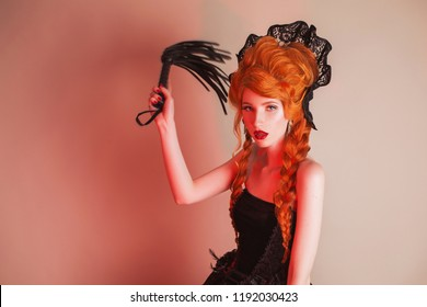 Gothic clothes. Young sexual redhead queen with hairstyle. Bdsm toy for fetish. Mistress with red hair. Vampire with pale skin. Outfit for playing fetish bdsm games. Sexual mistress in gothic dress.