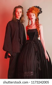 Gothic couple in halloween costume. Pale undead vampire in edwardian carnival clothes. Gothic costume for halloween party.