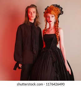 Gothic couple in a halloween costume. Pale undead vampire in dark victorian clothes. Redhead woman in black carnival dress. Gothic costume for halloween party. Victorian couple in studio