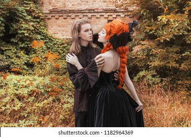 Gothic couple in a halloween costume. Pale undead vampire in edwardian clothes. Punk couple on autumn background. Gothic clothes for halloween party. Redhead punk woman in black edwardian dress.