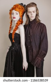 Gothic couple in halloween costume. Pale undead vampire in edwardian carnival clothes. Gothic costume for halloween party. Redhead woman in black carnival dress. Edwardian couple on dark background.
