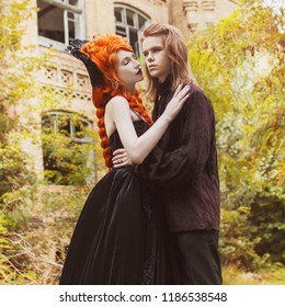Gothic couple in a halloween costume. Pale undead vampire in edwardian clothes. Gothic clothes for halloween party. Redhead woman vampire in black edwardian dress. Undead couple on autumn background.