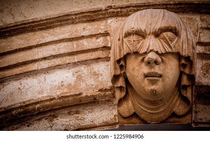 Gothic detail. Young woman portrait at the entrance of a 200 years old building in Ciutadella town, Menorca (Spain)