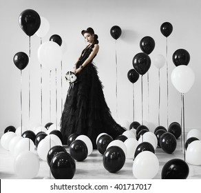 Gothic girl in black dress among black and white balloons.