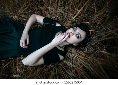 gothic guitar player girl with black hair at autumn yellow field