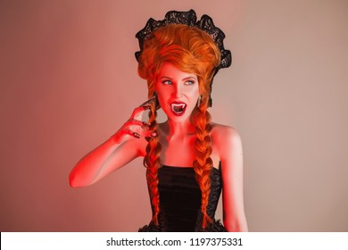 Gothic halloween clothes. Young eerie redhead queen with hairstyle. Death with red hair. Vampire with sharp fangs. Eerie outfit for halloween party. Death demon vampire in gothic dress.