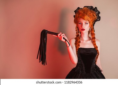Gothic halloween clothes. Young provocative redhead queen with hairstyle. Mistress with red hair. Vampire with pale skin. Mystical outfit for halloween party. Provocative mistress in gothic dress.