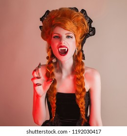 Gothic halloween clothes. Young terrible redhead queen with hairstyle. Demon with red hair. Vampire with sharp fangs. Terrible outfit for halloween party. Undead demon vampire in gothic dress.