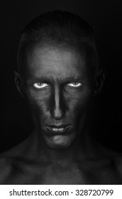 Gothic and Halloween theme: a man with black skin is isolated on a black background in the studio, the Black Death body art