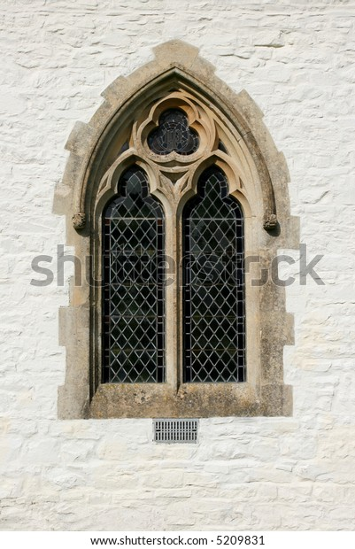 Gothic leaded glass window on the outside of a church set within a white washed stone wall.