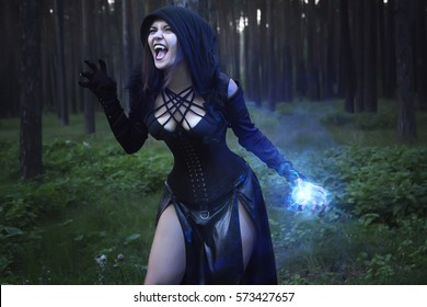 Gothic model in the woods, the blue lights. Vampire stories. The girl in a black hood and shouting blue conjures magic. Photo illustrations in fantasy style. photoshoot for Halloween