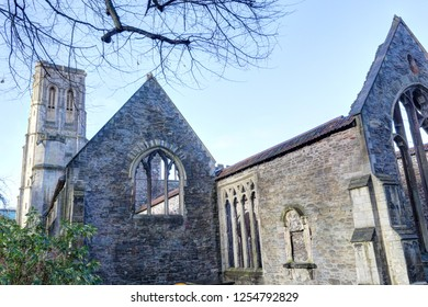 Gothic pointed arch windows on a stone wall, and bell tower, in the abandoned rumbled Temple Church in Bristol, in a sunny winter, in United Kingdom