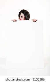 Gothic, raggedy ann style doll model behind blank white sign.  Your message or ad goes here.