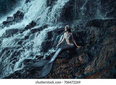 The gothic real mermaid is resting on the ocean shore. Wet Silver tail, the body is covered with scales. Creative colors. Queen of the sea, crown shells. Summer landscape a huge waterfall rock stone