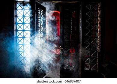 Gothic room with red illumination. Gothic room with columns and arches. Old Gothic hall. Rays of light beat through the bars in the door.