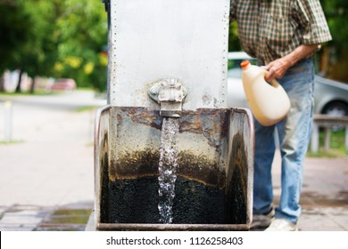 Gothic spigot installed on a flowing artesian wellhead. Selective focus. The blurry contours of a partially visible man holding a plastic demijohn, in the nearest surroundings.