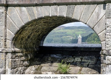 The gothic straining tower of Lake Vyrnwy framed by a dam arch in Wales, UK.