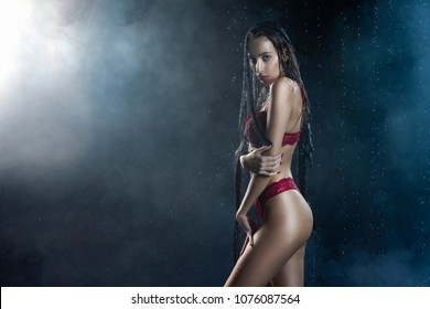 Gothic style young beautiful girl wearing a red lingerie and black veil on her head and face sensually posing in water drops and shows her butt in a theatrical smoke. Healthy smooth skin. Copy space