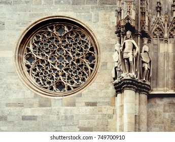 Gothic window on a facade of the St. Stephen's Cathedral. Rose Window and stone figures of catholic saints - architectural elements on the wall of medieval temple in Vienna, Austria.