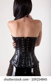 Gothic woman in black leather corset embracing herself