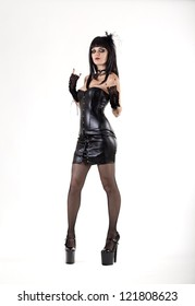 Gothic woman in sexy leather outfit, studio shot on white background