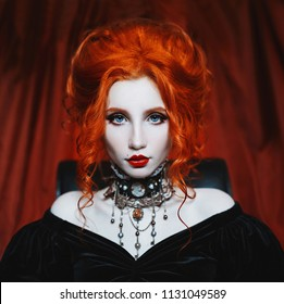 Gothic woman is a vampire with pale skin and red hair in a black dress and a necklace on her neck. Girl witch with vampire claws and red lips. Gothic look. Outfit for halloween.