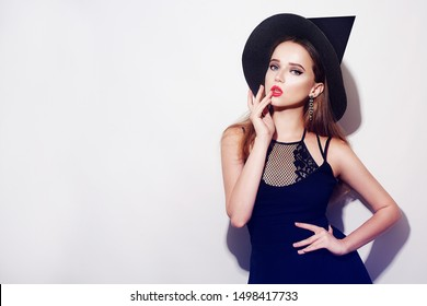Gothic young woman in witch halloween costume with hat standing over white background. Beautiful young girl in black dress and hat.  Party halloween.