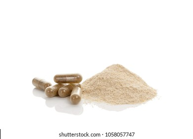 Gotu kola gel capsules and heap of powder. Herbal remedy. Isolated on white background.