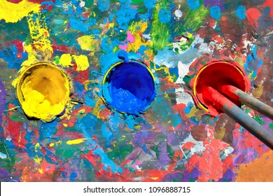 Gouache paint table with paint smears and cups with yellow, blue and red paints. Top view, two brushes in the cup containing in red paint.