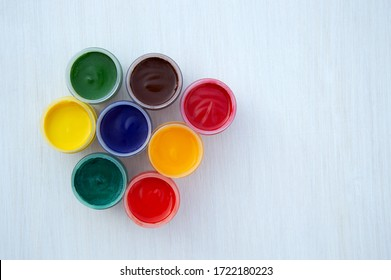Gouache paints in jars. Bright color. Red, pink, yellow, orange, blue and green colors in small jars. The view from the top. Flat lay