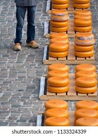 Gouda, Amsterdam, May 2016: Traditional Dutch clogs and stacked cheeses at the Gouda cheese market, Netherlands