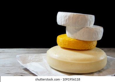 Gouda cheese, Kachotta cheese, Camembert cheese on parchment paper on a black background