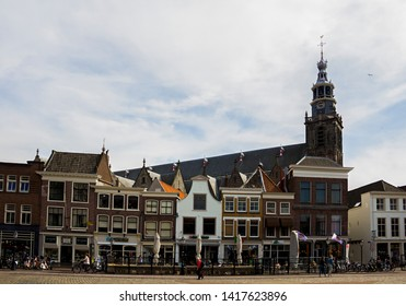 Gouda, Holland, Netherlands, April 23, 2019. The market square in Gouda old town, a street of dutch style facades of houses and view of the bell tower of Sint-Janskerk church (highest in the Netherlan