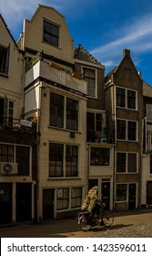 Gouda, Holland, Netherlands, April 23, 2019. The Gouda old town, a Typical street of dautch style facades of houses and a cyclist