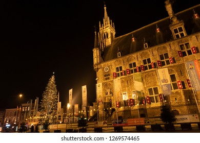 Gouda, The Netherlands - December 25 2018: Night shot of the ice skating rink around the medieval town hall with a lot of advertising flags, lights and a huge Chrismas tree.