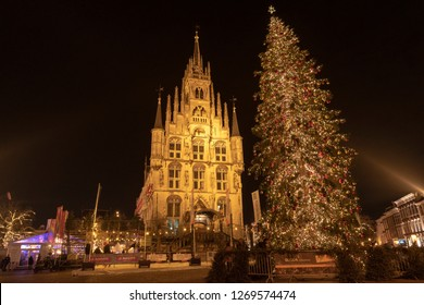 Gouda, The Netherlands - December 25 2018: The medieval town hall in the evening with a ice skating rink around it and a huge decorated Christmas tree in front.
