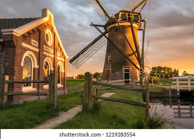 """Gouda, the Netherlands - June 11th  2017: Mill """"Mallemolen"""" and pumping station in Gouda at sunset."""