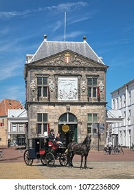 GOUDA, NETHERLANDS - MAY 24, 2015: Horse carriage with coachman and his assistant in front of the Waag. The Waag (or Kaaswaag) is a cheese weighing house built in 1668-1670 by design of Pieter Post.