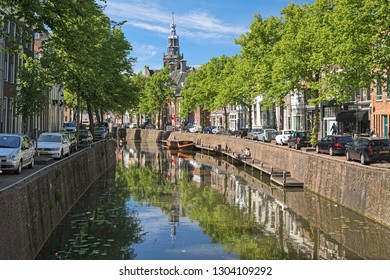 GOUDA, NETHERLANDS - MAY 24, 2015: View on the tower of Sint Janskerk (St John the Baptist Church) from the Nood-Godsbrug bridge across the Gouwe river in sunny day.
