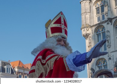 Gouda, The Netherlands - November 17 2018: Sinterklaas/ Saint Nicholas waves to the people on the market of Gouda, The Netherlands. On the background the old town hall.
