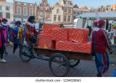 Gouda, The Netherlands - November 17 2018: Black Petes carrying large gifts on a cargo bike at the Gouda market.